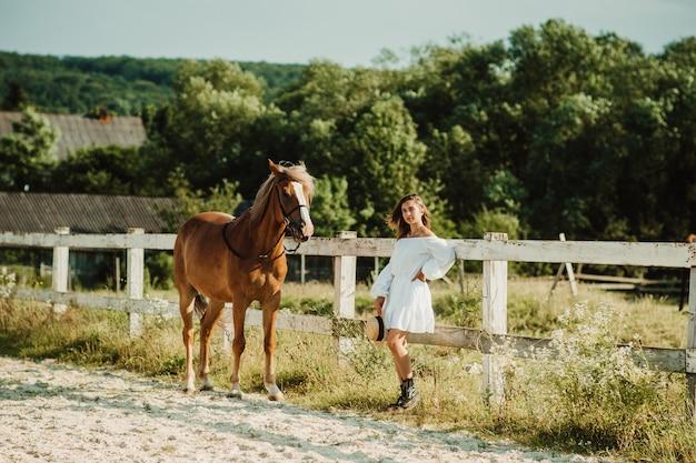 Piękna hipis dziewczyna z koniem na tle ranczo, widok z przodu. dziewczyna w kapeluszu. nieostrość