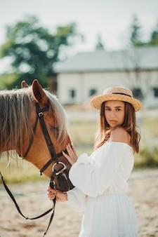 Piękna hipis dziewczyna z koniem na tle ranczo, widok z przodu. dziewczyna w kapeluszu.