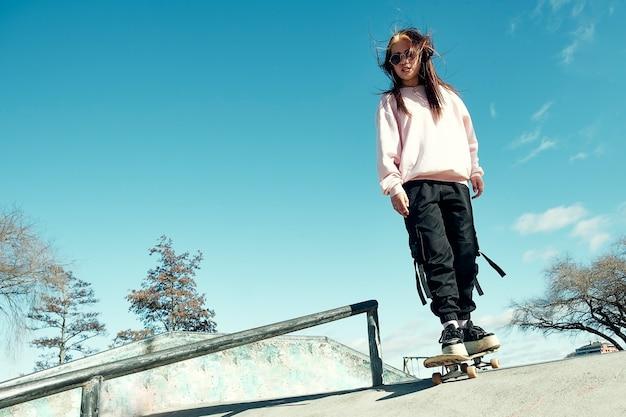 Piękna hipster dziewczyna w swobodnym ubraniu i długich prostych włosach jeździ na rampie z deskorolką w skate parku