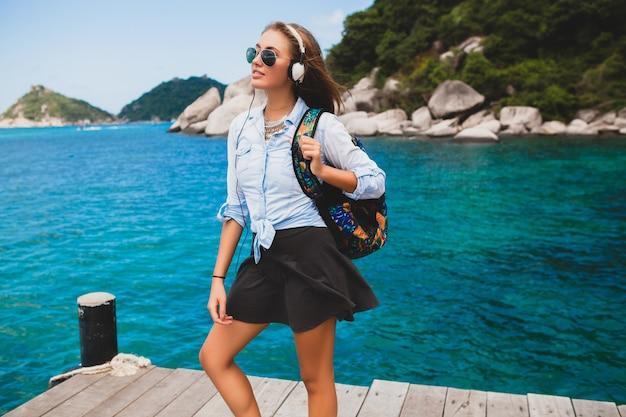 Piękna hipster kobieta podróżująca po świecie z plecakiem, uśmiechnięta, szczęśliwa, pozytywna, słuchająca muzyki w słuchawkach, tło błękitnego oceanu tropikalnego, okulary przeciwsłoneczne, sexy, letnie wakacje,