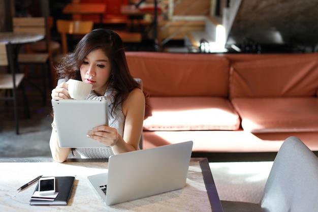 Piękna i atrakcyjna azjatykcia kobieta, długie włosy w szarej przypadkowej sukni pracuje na stole i pije kawę rano