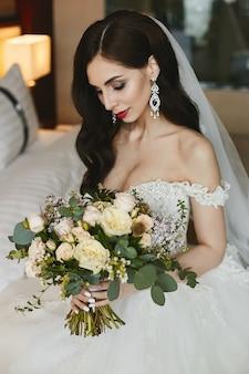 Piękna i cycata modelka z jasnym makijażem i luksusowymi dużymi kolczykami z brylantami w modnej sukni ślubnej z dużym bukietem kwiatów w rękach
