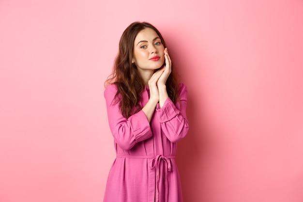 Piękna i delikatna kobieta dotykająca idealnie nawilżonej twarzy jasnym makijażem, trzymająca dłoń na policzku, wpatrująca się w kamerę, stojąca nad różową ścianą.