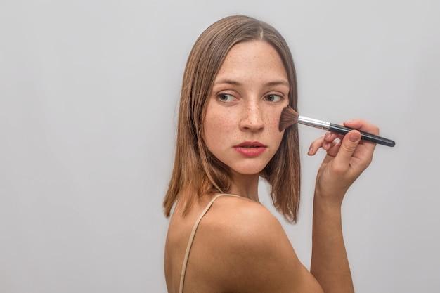 Piękna i miła młoda kobieta stoi i pozuje. na pisklęta nakłada pędzel do makijażu. patrzy w lewo i odwraca się.