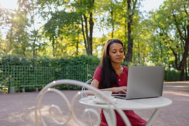 Piękna i młoda afrykańska kobieta z tysiąclecia w miejscu publicznym pracująca na laptopie