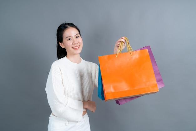 Piękna i młoda azjatka trzymająca torby na zakupy