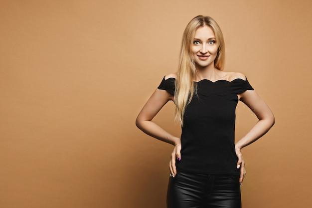 Piękna i młoda blondynka modelka o szczupłym idealnym ciele w czarnych skórzanych spodniach i czarnej bluzce pozującej przy pomarańczowej ścianie, izoluj