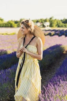 Piękna i młoda dziewczyna na polu pełnym lawendowych kwiatów