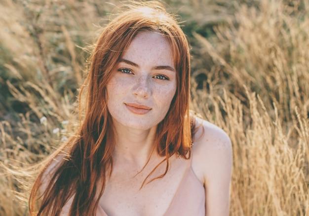 Piękna i młoda imbirowa kobieta z naturalnymi piegami na twarzy