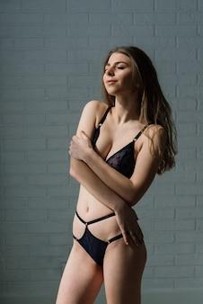 Piękna i młoda kobieta pozowanie w czarnej seksownej bieliźnie. vintage tło wnętrza i retro.