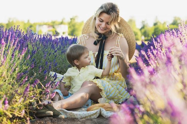 Piękna i młoda kobieta ze swoim uroczym synkiem na lawendowym polu