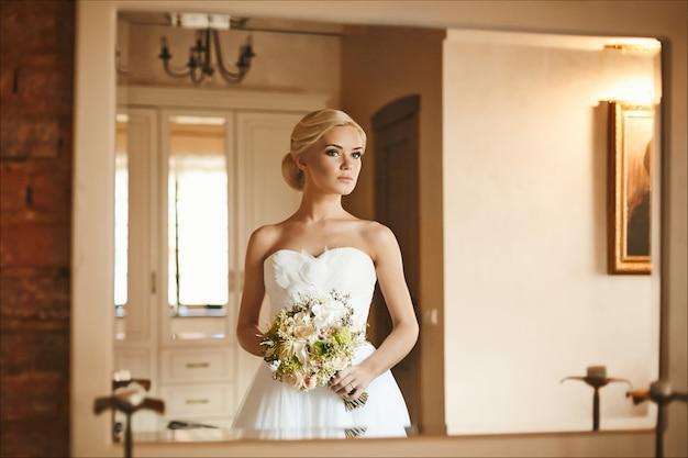 Piękna i modna blondynka modelka z fryzurą ślubną w modnej sukni z bukietem kwiatów w dłoniach, rano przygotowanie młodej panny młodej do ślubu