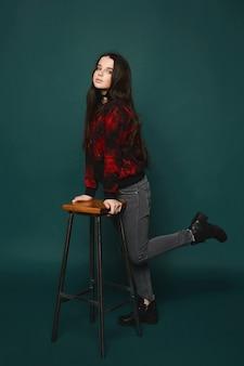 Piękna i modna brunetka modelka w stylowych szarych dżinsach i czarnej bluzie z czerwonym wzorem na ciemnozielonym tle