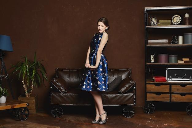 Piękna i modna modelka brunetka w niebieskiej sukience pozuje we wnętrzu retro