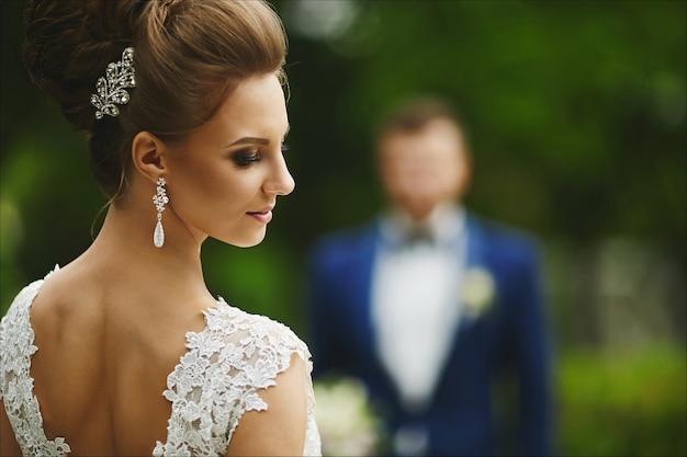 Piękna i modna modelka brunetka z jasnym makijażem i fryzurą ślubną