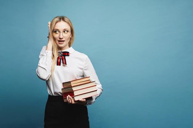Piękna i modna zdziwiona blondynka modelka w okularach, w stylowej bluzce i czarnej koronkowej spódnicy, ze stosem książek, na białym tle