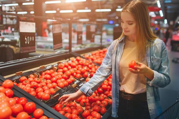 Piękna i niesamowita dama jest w sklepie brutto i wybiera pomidory do kupienia. wybrała jednego pomidora i trzyma go w dłoni. ścieśniać.