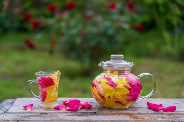 Piękna i pachnąca herbata z żółtych, różowych i czerwonych płatków róż w szklanym czajniczku i kubku w letnim ogrodzie na drewnianym stole. bliska ziołowa herbata kwiatowa z płatków róży na tle przyrody