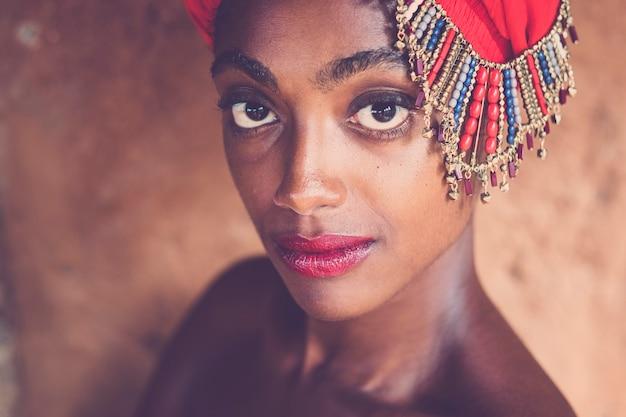 Piękna i piękna czarna afrykańska dziewczyna w tradycyjnym modnym kapeluszu z klejnotami pozująca z dużymi cudownymi oczami i czerwoną szminką - młodość i atrakcyjna afrykańska kobieta