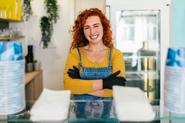 Piękna i pozytywna ruda kobieta imbir uśmiechając się i pracując w ręcznie robionych lodach. pozuje ze skrzyżowanymi rękami i patrzy w kamerę..