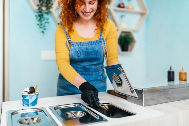 Piękna i pozytywna ruda kobieta imbir uśmiechając się i pracując w ręcznie robionych lodach. przygotowuje i podaje pyszne słodkie jedzenie.
