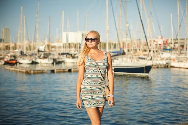 Piękna i seksowna blondynka modelka w modnej krótkiej sukience i stylowych okularach przeciwsłonecznych pozuje na nabrzeżu przed jachtowcami.
