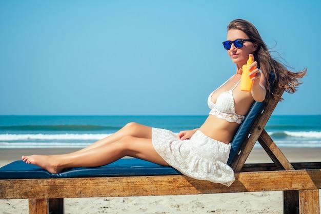 Piękna i seksowna młoda kobieta nakłada krem przeciwsłoneczny na ciało na morzu.