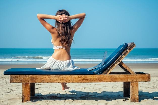Piękna i seksowna młoda kobieta siedzi na leżaku z laptopem nad morzem.