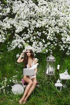 Piękna i seksowna modelka o idealnym ciele w stylowej bieliźnie z koroną na głowie pozującą z gołębiami pod kwitnącym drzewem w zielonym lesie