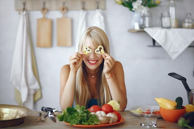 Piękna i sportowa dziewczyna w kuchni z warzywami
