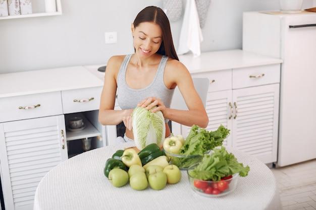 Piękna i sportowa kobieta w kuchni z warzywami