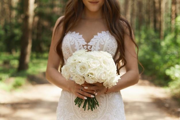 Piękna i stylowa brunetka modelka w modnej koronkowej sukni z bukietem kwiatów w dłoniach i pozująca w lesie wczesnym rankiem