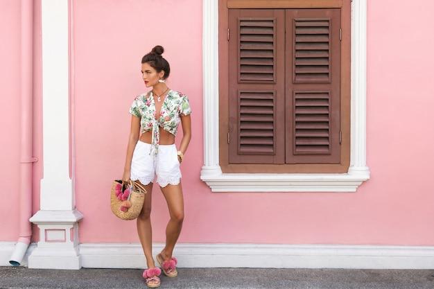Piękna i stylowa kobieta ubrana w letnie ubrania pozuje obok domu z różową ścianą