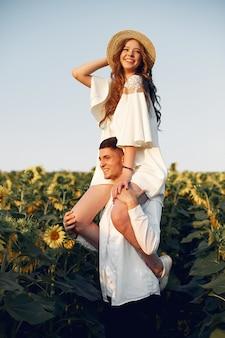 Piękna i stylowa para w polu z słonecznikami