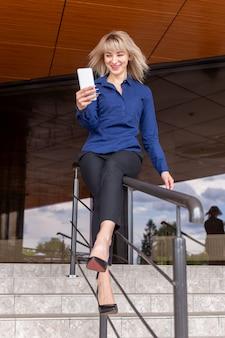 Piękna i szczęśliwa blondynka z telefonem