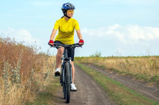 Piękna i szczęśliwa kobieta rowerzysta jeździ na rowerze na drodze w przyrodzie. zdrowy styl życia i sport. wypoczynek i hobby