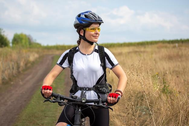 Piękna i szczęśliwa kobieta rowerzysta jeździ na rowerze na drodze w przyrodzie. zdrowy styl życia i sport.