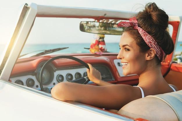 Piękna i szczęśliwa kobieta wśrodku retro samochodu