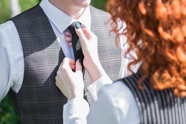 Piękna i szczęśliwa młoda para w przyrodzie. zbliżenie dłoni żony mocującej krawat do męża