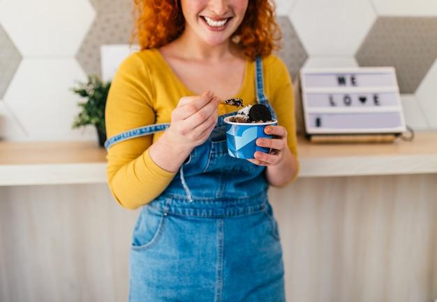 Piękna i szczęśliwa ruda kobieta, ciesząc się jedzeniem pysznych lodów ręcznie robionych.