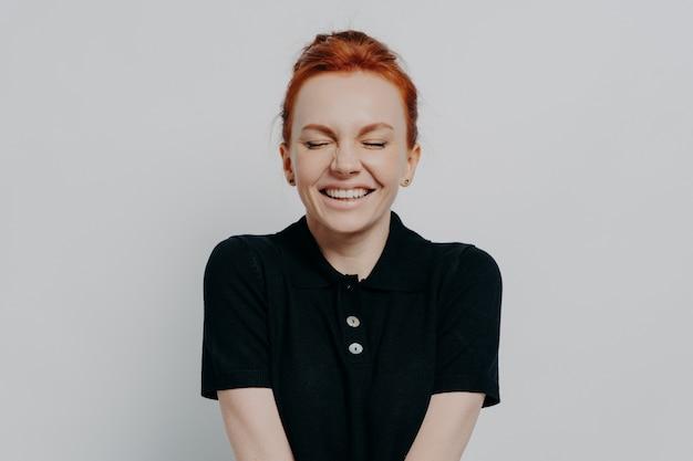 Piękna i szczęśliwa zadowolona rudowłosa kobieta z zamkniętymi oczami i ząbkowanym uśmiechem pozowanie na szarej ścianie. wesoła podekscytowana kobieta okazująca pozytywne emocje i szczęście, ubrana swobodnie
