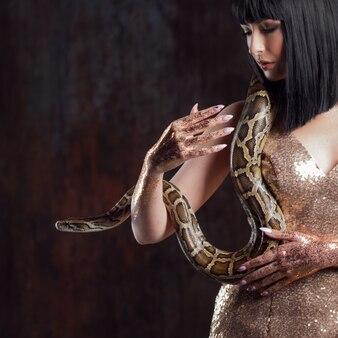 Piękna i tajemnicza brunetka w złotej sukience z wężem