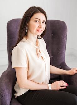 Piękna i urocza brunetka w lekkiej bluzce siedzi na krześle, uśmiecha się i patrzy w kamerę.