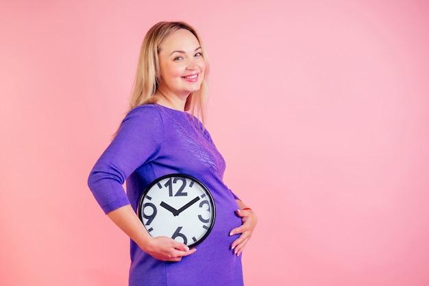 Piękna i uśmiechnięta blondynka w ciąży trzyma zegar w ręce w studio na różowym tle. czas na koncepcję urodzenia.