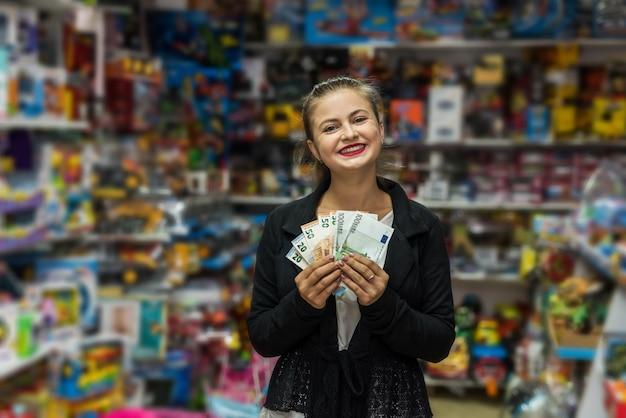 Piękna i uśmiechnięta kobieta trzyma banknoty euro