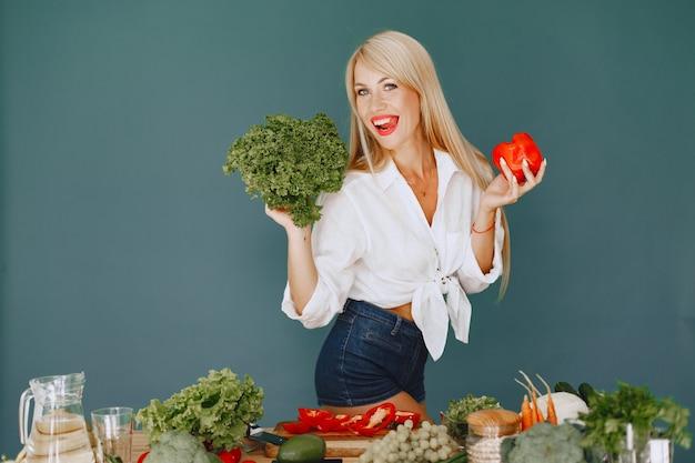Piękna i wysportowana dziewczyna w kuchni z warzywami