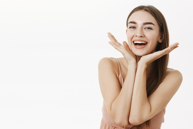 Piękna i zdrowa czarująca kobieta o naturalnej urodzie trzymająca dłonie w pobliżu linii żuchwy i uśmiechnięta szeroko zadowolona z doskonałej kondycji skóry, pozująca wesoło