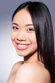 Piękna i zdrowa. portret pięknej młodej i bez koszuli azjatyckiej kobiety patrzącej na kamerę i uśmiechającej się stojąc na szarym tle