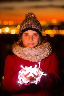 Piękna iluminowana kobieta trzymająca światło led na czerwonym płaszczu w noc bożego narodzenia.