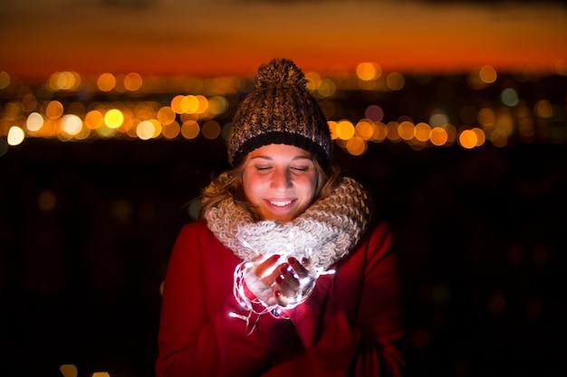 Piękna iluminująca kobieta trzyma światło w noc bożego narodzenia.